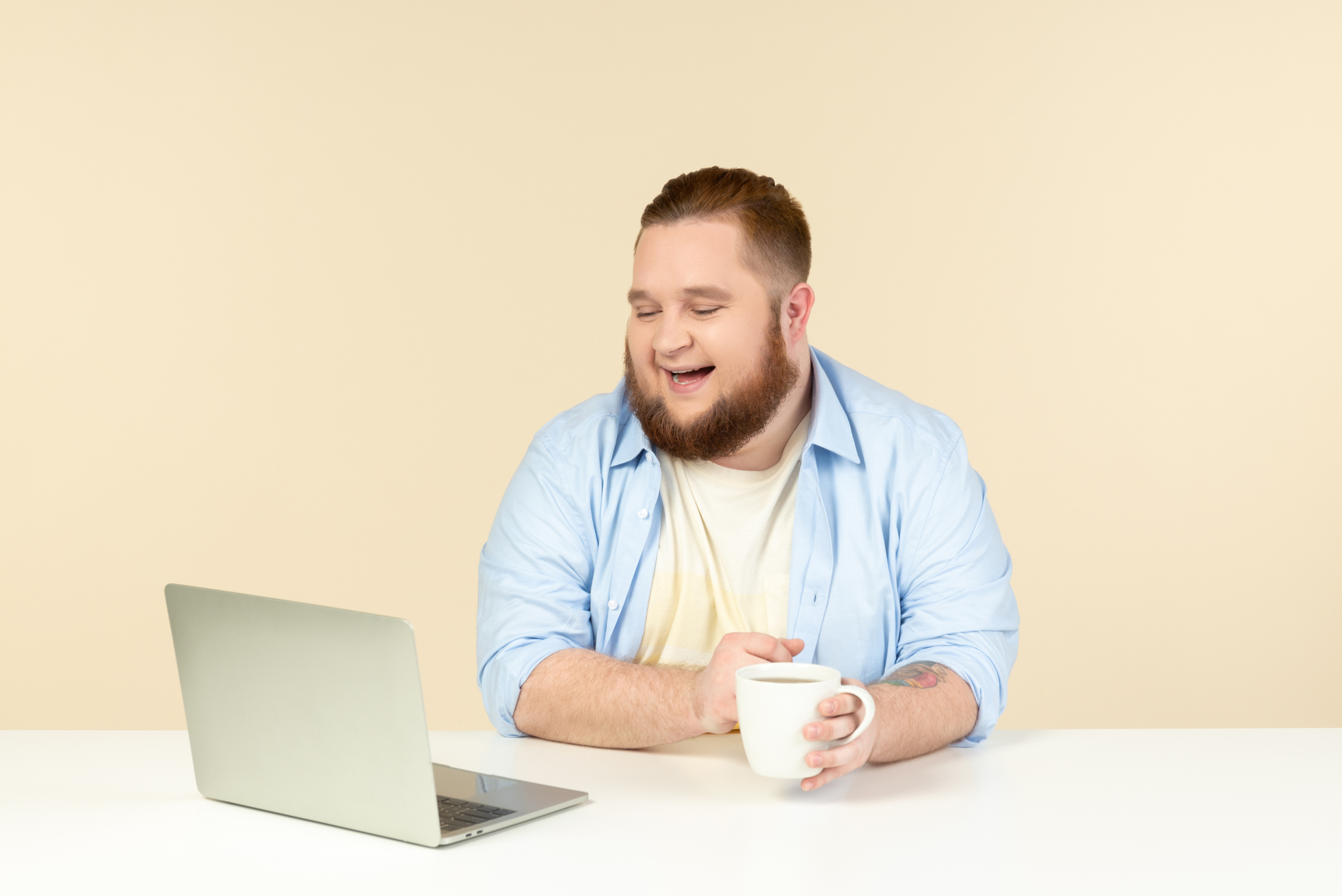 Photo of a laughing young overweight man looking at laptop and having tea